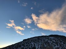 Sunrise over snowy butte Stock Image