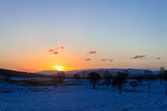 Sunrise over snowy fields Stock Images