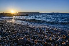 Sunrise over a stone beach in Rabac Croatia royalty free stock images