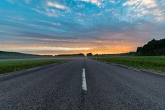 Sunrise over a straight road through green fields. In sweden royalty free stock images