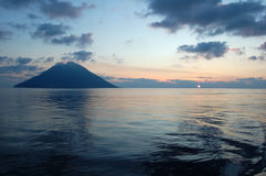 Sunrise over Stromboli island. Stromboli is an island in the Tyrrhenian Sea, off the north coast of Sicily, containing one of the three active volcanoes in Royalty Free Stock Photos