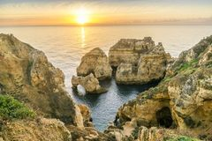 Sunrise over stunning cliffs and arches in Ponta da Piedade, Lag. Stunning cliffs and arches in Ponta da Piedade in the early morning, Lagos, Algarve, Portugal Stock Photos