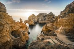 Sunrise over stunning cliffs and arches in Ponta da Piedade, Lag. Stunning cliffs and arches in Ponta da Piedade in the early morning, Lagos, Algarve, Portugal Royalty Free Stock Image