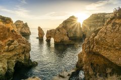 Sunrise over stunning cliffs and arches in Ponta da Piedade, Lag. Stunning cliffs and arches in Ponta da Piedade in the early morning, Lagos, Algarve, Portugal Royalty Free Stock Photo