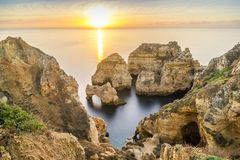 Sunrise over stunning cliffs and arches in Ponta da Piedade, Lag. Stunning cliffs and arches in Ponta da Piedade in the early morning, Lagos, Algarve, Portugal Royalty Free Stock Images