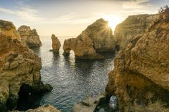 Sunrise over stunning cliffs and arches in Ponta da Piedade, Lag. Stunning cliffs and arches in Ponta da Piedade in the early morning, Lagos, Algarve, Portugal Stock Image