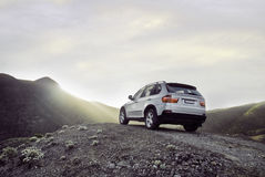 Sunrise over suv. Back of unmarked silver modern 4wd sports utility vehicle on hill with sunset sunrise royalty free stock image