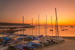 Sunrise over Swanage piers illuminated by the orange pre-dawn Royalty Free Stock Photos