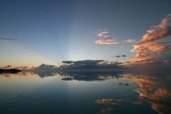 Sunrise over tahiti. With clouds reflecting on the lagoon Royalty Free Stock Photography