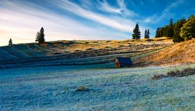 Sunrise over terraced fields. Terraced field with hoarfrost at a wood house in a  rural landscape Royalty Free Stock Photos