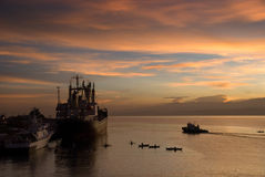 Sunrise over tropical port. Flamboyant colorful early exotic sunrise in the dawn over a tropical port with a cargo ship and small beggar's and fishermen's boats stock images