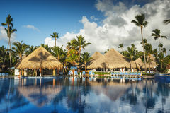 Sunrise over tropical swimming pool in luxury resort, Punta Cana. Tropical swimming pool and palm trees in luxury resort Royalty Free Stock Photography