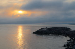 Sunrise over unused derelict pier in Grand Bank, Newfoundland. Warm sunlight shines through cloudy foggy mist. Shadowy derelict boulder pile pier extends into royalty free stock photography