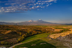 Sunrise over a valley. With snow-covered mountain peaks on the horizon Royalty Free Stock Photo