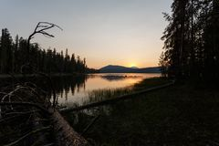 Sunrise over a volcano reflects  into an alpine lake in northern California Royalty Free Stock Photo