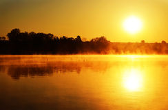 Sunrise over the water. Sunrise over the lake quiet;  Reflection of the sun in water, orange tone Stock Photos