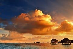 Sunrise over water bungalows in Maldives. Sunrise over water bungalows on a cloudy day at the end of rainy season in Maldives stock photos