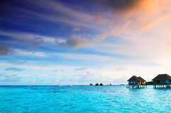 Sunrise over water bungalows in Maldives. Sunrise over water bungalows on a cloudy day at the end of rainy season in Maldives stock photography