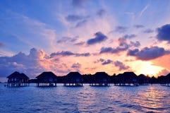 Sunrise over water bungalows in Maldives. Sunrise over water bungalows on a cloudy day at the end of rainy season in Maldives stock image