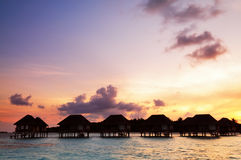 Sunrise over water bungalows in Maldives. Sunrise over water bungalows on a cloudy day at the end of rainy season in Maldives royalty free stock image