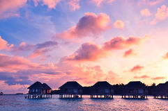 Sunrise over water bungalows in Maldives. Sunrise over water bungalows on a cloudy day at the end of rainy season in Maldives royalty free stock images
