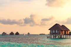 Sunrise over water bungalows in Maldives. Sunrise over water bungalows on a cloudy day at the end of rainy season in Maldives stock images