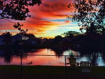 Sunrise over water. The sun rises over a canal in Florida, orange skies, fence peaceful, tranquility inspiring Stock Photography