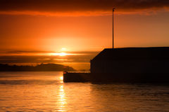 Sunrise over a wharf building. In Auckland harbour, New Zealand Stock Photo
