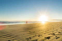 Sunrise over wide flat sandy beach at Ohope Whakatane. Golden beach hue at sunrise over wide flat sandy beach at Ohope Whakatane, New Zealand with distant Stock Photo