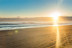 Sunrise over wide flat sandy beach at Ohope Whakatane royalty free stock photo