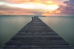 Sunrise over wooded bridge on the beach in Thailand stock photo