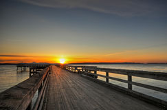 Sunrise over a wooden pier, Sidney, BC. A beautiful spring sunrise peaks over a wooden fishing pier on the west coast of Canada Royalty Free Stock Images
