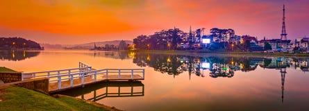 Sunrise over Xuan Huong Lake, Dalat, Vietnam. Panorama. Amazing view of sunrise over Xuan Huong Lake, Dalat, Vietnam. Pier on the foreground. Landscape photo royalty free stock images