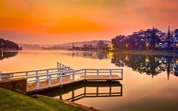Sunrise over Xuan Huong Lake, Dalat, Vietnam. Panorama. Amazing view of sunrise over Xuan Huong Lake, Dalat, Vietnam. Pier on the foreground. Landscape photo stock images