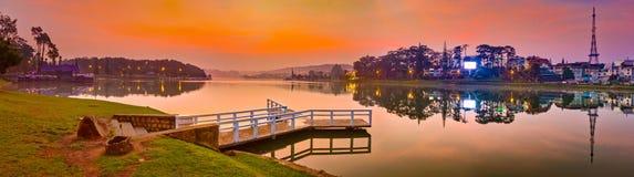 Sunrise over Xuan Huong Lake, Dalat, Vietnam. Panorama. Amazing view of sunrise over Xuan Huong Lake, Dalat, Vietnam. Pier on the foreground. Landscape photo stock image