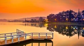 Sunrise over Xuan Huong Lake, Dalat, Vietnam. Panorama. Amazing view of sunrise over Xuan Huong Lake, Dalat, Vietnam. Pier on the foreground. Landscape photo royalty free stock photos