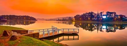 Sunrise over Xuan Huong Lake, Dalat, Vietnam. Panorama. Amazing view of sunrise over Xuan Huong Lake, Dalat, Vietnam. Pier on the foreground. Landscape photo royalty free stock image