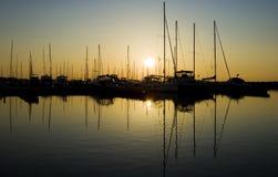 Sunrise over yacht marina. Scenic view of sunrise over yacht marina silhouetting boats Stock Image