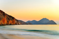 Sunrise over Zighy Bay. Scenic view of sunrise over Zighy Bay with beach in foreground, Oman Royalty Free Stock Images