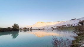 Sunrise in Pamukkale (Turkey) with the white hill and its reflection in the natural pool. Timelapse, 4k stock video