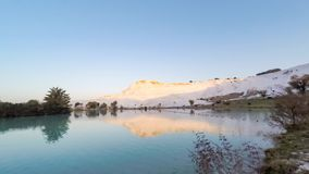 Sunrise in Pamukkale (Turkey) with the white hill and its reflection in the natural pool. Timelapse, 4k stock video footage