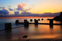 Sunrise Paradise, Coogee Beach, Australia. Spectacular sunrise at the Coogee Baths, south side, Coogee, Australia.  The two pools are perched into the cliff face Royalty Free Stock Image