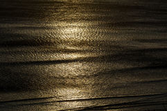 Sunrise patterns on the sea. Light patterns from a sunrise on the ocean giving golden ripples Royalty Free Stock Photo