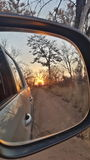 Sunrise. Peeking through vehicle mirror Royalty Free Stock Photos