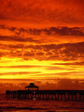 Sunrise with pier. A fishing pier reaching into the ocean as the sun rises in fiery reds and golds. Portrait perspective of Deerfield Beach Florida pier stock image
