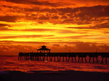 Sunrise with pier. A fishing pier reaching into the ocean as the sun rises in fiery reds and golds. Landscape perspective of Deerfield Beach Florida pier stock images