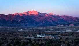 Sunrise on Pikes Peak above Colorado Springs, Colorado. The summit of Pikes Peak glows in the morning sunrise as the streets and business office are below the Stock Photos