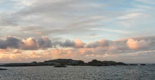 Sunrise with pink sky and clouds over the ocean and archipelago of Faerder National Park, Norway, panorama. Sunrise with pink sky and clouds over the ocean and Royalty Free Stock Image