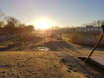 Sunrise at playground. Sunrise at a cold winterday on a silent playground in Holland Royalty Free Stock Image