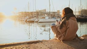 Sunrise in port and girl. Backview on girl in warm coat sitting alone in port and taking picture of sunrise in front of parked yachts in small marina at early stock footage